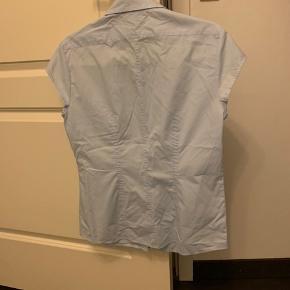 Lyseblå skjorte i figurfacon fra Eterna str 38. Aldrig brugt.  Køber betaler Porto.