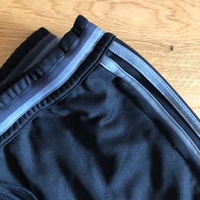 Unisex, altså både til mænd og kvinder   Velkendte adidasbukser som både kan bruges som træningsbukser og jogging/afslapningsbukser   Str.: M  Farve: sort m. grå striber   Stand: fremstår som nye