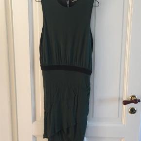 Varetype: Mini Farve: Grøn  Smuk kjole i en lækker blød kvalitet. Kjolen er tætsiddende med drapering forneden og sort elastik i taljen. Ryggen er i sort stof med slids. Brugt få gange.