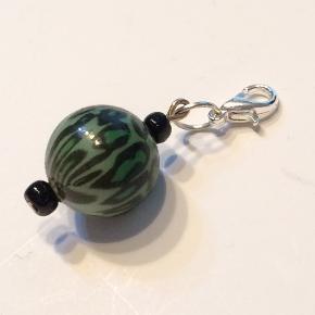 Charms, perler, Walina  Vedhæng til tasker punge halskæder  Grøn charm, med matchende perler.  Brug den som pynt til: - din lynlås til dit penalhus, taske eller pung - din nøglering - din eksisterende halskæde  I alt er den 3,5 cm lang.  Jeg kan handle med mobilpay: Jeg sender gerne med post nord til din postkasse (+10 kr 5 dages leveringstid eller 29 kr 1 dags leveringstid), hvis du ikke kigger forbi og henter den. Jeg kan handle via Tradono med DAO pakkepost (+32 kr), hvor du afhenter pakken ved ønsket DAO udleveringssted  Mvh Lise