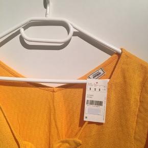 Sød gul top, med bind foran.