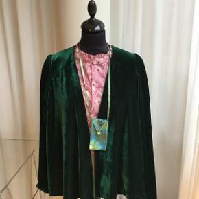 Håndsyet cardigan jakke i smaradgrøn velour fra den århusianske designer Moluu. Den har læg på skuldrene og faconen er rundskåret, så den falder blødt. Str. 38/40. På fotos stylet med en skjorte i Liberty stof.