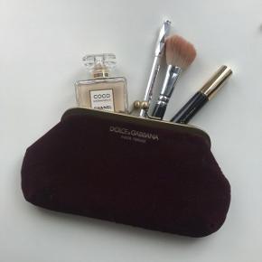 Lækker velour og indvendig satin clutch fra Dolce & Gabbana (farven ses på billede 2 og frem)   Købt i forbindelse med noget makeup, så derfor står der ikke til salg i mærket inde i tasken.  Kan bruges som makeuppung, clutch eller anden opbevaring. Der er plads til en iPhone 7 i, så derfor kan en større telefon ikke passe, hvis den ønskes brugt som clutch  Np: vides ikke Mp: bud fra 150kr Stand: brugt meget få gange ellers blot ligget Medfølger: intet  Kan sendes med DAO eller hentes i Esbjerg - kom gerne med et bud :))