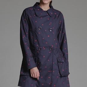Brand: Mademoiselle Yeye Varetype: Regnjakke Farve: Mørkeblå  Fed regnjakke med kysmundsmotiv 💋  i A-form med lynlås og store knapper. Hætten kan tages af. Jakken er lidt stor i størrelsen