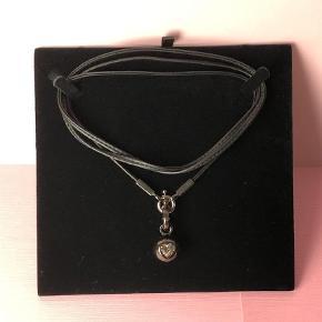🛍 Brug KØB-NU funktionen ved køb 🛍  Smuk halskæde med vedhæng fra DYRBERG KERN i sortgrå metal. Lædersnøren har et rundt øsken som kan åbnes. Vedhænget er en stor rund kugle med hjerteformet Swarovski krystal samt rundt lukkeøsken som kan åbnes.   Lædersnøren kan anvendes som en lang halskæde hvor vedhænget hænger ved maven eller rundt 2 gange som alm kæde eller 3 gange som en kort kæde. Vedhænget kan hægtes af, og lædersnøren kan også bruges som armbånd.   Perfekt gaveidé. Smykkepose og certifikat fra Dyrberg/Kern medfølger ved salget.