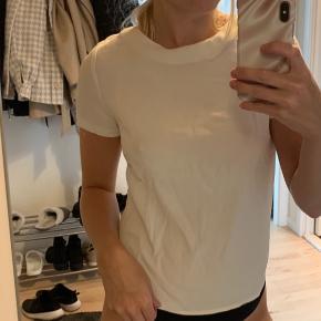 T-shirt i finere materiale (polyester) agtig.  Pænt til en blazer eller finere tøj.   Har lynlås i nakken.   Er meget lille i str. så den passer en xs-s pige.