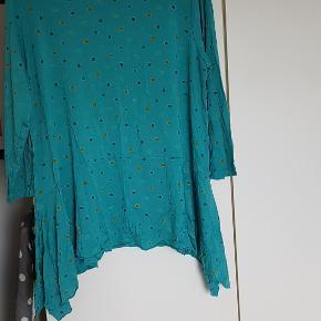 """Sød tunika med fine prikker og bred """"flæse"""" nederst, der er længere i siderne end foran og bagpå. Længde fra skulder: ca. 70-81 cm Bryst: ca. 2 x 60 100% tencel"""