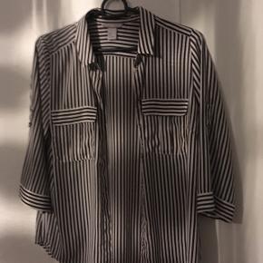 """Super flot sort/hvid stribet skjorte, i noget meget let og silkeagtigt stof, perfekt til forår og sommer! Skjorten har nogle rigtig fine detaljer, fx guldfarvet knapper, brystlommer og at man kan """"binde"""" ærmerne op i nogle fine små guldfarvede ringe (se billede) så de bliver kortere med et lille opslag.  Lidt lille i størrelsen, vil passe rigtig fint til en lille M/38 og også til en S/36.  Har kostet omkring 180-200 kr.   Hvis den skal sendes, betaler køber fragt.  Mvh Betina Thy"""