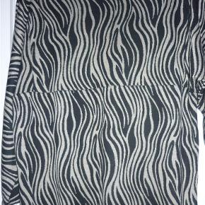 Klassisk masai tunika i bomuld m. elestan. Har 3/4 ærmer. Længde 64 cm.  Tunika Farve: Sort/sand