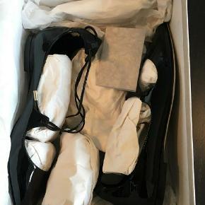 Super flotte lak ballerina sandaler med snøre. Str 37 og almindelig i str.  Kun brugt 1 gang udendørs. Købt i Illum for ca. 3-4 år siden, og har ligget i sin æske i skabet siden, da det var et fejlkøb.  Pris: 1000kr eksl. Porto