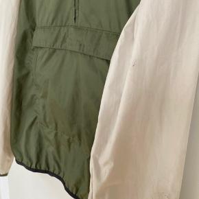 """Sælger denne The North Face """"Fanorak"""", som kan rulles sammen i sin egen lomme og bruges som bæltetaske. Den fungerer som windbreaker og kan også holde let regn ude - skal dog ikke forveksles med en decideret regnjakke.   Har tegn på slid - se billeder - men er derudover i fornuftig stand."""
