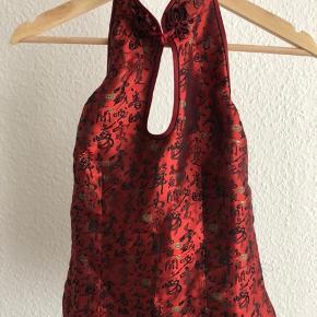Kinesisk silke. Aldrig brugt. Dyb ryg, lynlås i siden. Lukkes i nakken og foran på brystet