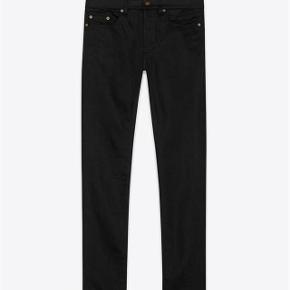 Brand: Saint Laurent Varetype: D02 Black Skinny Jeans Størrelse: 27 Farve: Sort Oprindelig købspris: 3.000 kr. Kvittering haves. Prisen angivet er inklusiv forsendelse.  Sorte Saint Laurent skinny jeans, model D02.  Størrelse 28 Low wasted skinny fit i sort raw denim. Ben åbning 15.5cm Fremstår fuldstændig ubrugt.  Købt i Paris og kommer i perfekt købt stand med original tag samt kopi af kvittering.  Nypris 3.000kr Sælges for 1.200kr inkl forsendelse