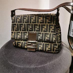 Vintage Fendi skuldertaske.  BROWN ZUCCA CANVAS BAGUETTE MAMMA  Sælger den klassisk vintage Fendi taske.  Tasken er i fantastisk stand og man kan kun se tegn af brug på spændet og en enkle lille plet nede i taske. Tasken kommer uden tilbehør.   Mål:   Mål: 26 x 19 cm Skulderrem: 22 cm  Vejlende pris: 6500 kr. Mp: 5000 Står 100% indenfor ægthed og laver slutseddel