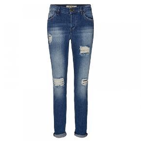 **Nye fede jeans fra Mos Mosh** Seje 5-lommers jeans fra Mos Mosh. Bukserne har slidte detaljer med huller og broderet fjer på baglommerne. Der er stof på bagsiden af hullerne. Str. 27 - er i butikkerne nu. Helt nye og med mærke på endnu. Kvalitet: 99% bomuld, 1% elastan Farve: 410 Blue Denim