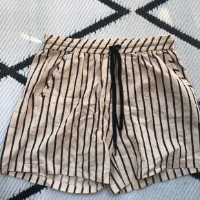 Fine shorts med lommer for og bag samt snører, de er en slags bomuld der skal se lidt slidt ud a la hør, striben er sort med en meget tynd rød stribe udenom :)