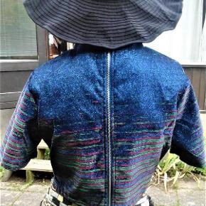 Brand: Glamorous - blå - party Varetype: bluse - fancy metalic glimmer bluse Farve: metalic blå  Tætsiddende festlig bluse , med lynlås lukning i ryggen . polyester . Stoffet er i blå glimmer , men har andre farvede metal tråde i hele bunden , man ser i forskellige vinkler .  Måler ca 46 x 2 = 92 cm i brystvidde . Længde er ca 43 cm . Forstykke har rundnet kant forneden og har indsnit ved bryst . Ærmer måler ca 28 cm .