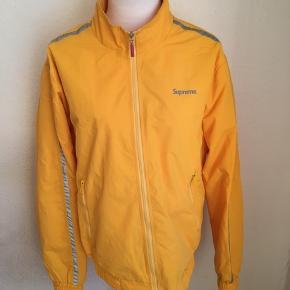 Supreme track jakke i gul med refleks detaljer. Størrelse medium.