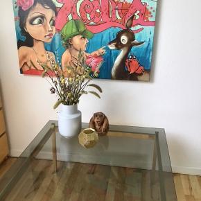 Det smukkeste retro messingbord med smuk røgfarvet glasplade.    Dejlig stort bord som måler 89,50 x 89,50 og 46,50 i højden.  OBS. Pladen har en lille skade i det ene hjørne, se billede. Men det er uden betydning.   Generelt et flot bord, som kun har nogle få ridser.   Afhentes i Tilst.  Selve stellet kan skilles ad i 4, og er nemt at samle igen.   Det smukke Coco Electra billede er også til salg, se seperat annonce.