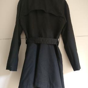 Helt sort trenchcoat fra Bruuns Bazaar. Den er helt sort i virkeligheden, men mit kamera vil ikke vise det ordentligt på billedet forfra.  Den har kun været brugt meget få gange.
