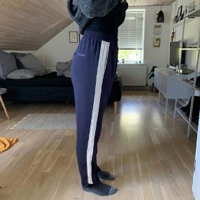 """Blå/beige løstsiddende, """"silke"""" bukser fra H&M. Næsten ikke brugt. """"Modellen"""" er normalt en str 36-38. Prisen er eks Porto."""