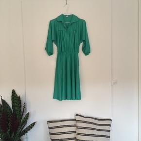 Grøn vintage kjole fra Amsterdam. Har krave og fine detaljer ved brystet, brede trekvartlange ærmer og elastik i indsnittet i taljen. God vidde i skørtet. Materialet er polyester.  Jeg har aldrig selv brugt den, da den desværre er lidt for stor.