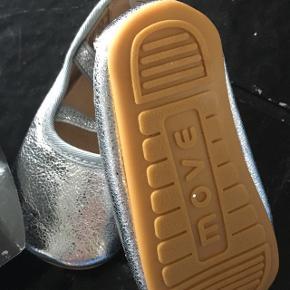 NMM hjemmesko fra Move by Melton, sølvfarvet med kryds i søvlglimmer elastik hen over vristen.  Prisen er plus porto eller afhentning i Varde. Sender med post nord eller dao.
