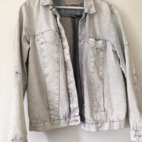 Virkelig fed denim jakke fra Calvin Klein i størrelse M. Den er købt i deres butik i London, og kun brugt 1 gang. Jakken er af noget helt specielt denim, som ligesom er blevet malet hvid og derfor har den forskellige farver af hvid/gul lidt forskellige steder. Obs. Der er en plet på jakken som ses på billede 3, som jeg ikke kan få af, men den er lille og bemærkes ikke tydeligt:)