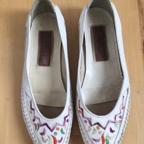 Super cool flade vintage moccasin sko / ballerinasko med i hvid med smukke multifarvede broderede detaljer. Det er en håndsyet moccasin fra det amerikanske mærke Preston. 100% ægte læder. Str. 39. Kom med et bud.  Varen befinder sig i 9520 Skørping. Sender med DAO.  Se også min øvrige annoncer. Jeg sælger tøj, sko og accessories. Pt er min shop fuld af vintagekup, high street fund og mærkevarer i mange forskellige str. Kig forbi og spøg endelig!!