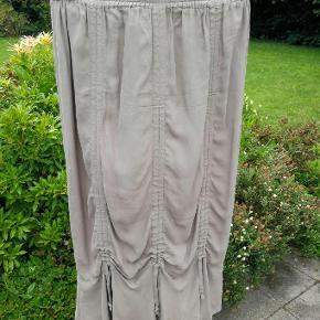 Masai nederdel str. M  Nederdeln har elastik i taljen - den har draperinger nederst på skørtet både for og bag, hvor man selv kan justere hvor meget drapering man ønsker  Livvidde uden at strække 74 cm  Længde. 84 cm  Hoftevidde ca. 116 cm