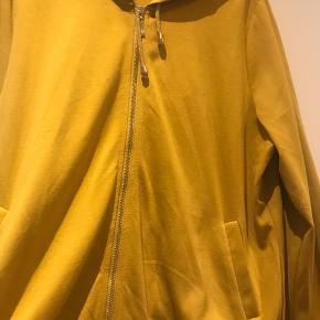 Sweetshirt karry farvet med hætte og lynlås . Lækker viskose Jersey kvalitet .  Ny pris 550 kr  Str S ( 42-44 )   1/2 bryst 62 cm  Længde 70 cm