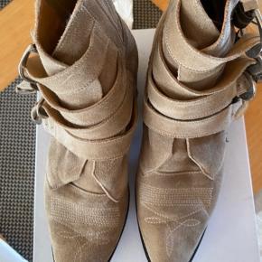 De har lidt slid på indersiden af begge støvlerne, som er kommet i forbindelse med brug. Jeg har ikke forsøgt at fjerne det, da det ikke ses tydeligt ved brug.  Både sål og hæl er blevet forsålet.   Bud under 800kr vil blive ignoreret.   Sendes på købers regning. Og sælger gennem trendsales.   Æske medfølger.