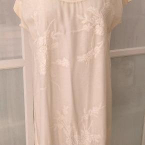 Bytter ikke.   Plus pakkeporto kr. 38,- uden omdeling, forsikret. Elegant kjole fra Gustav str. 42.  Kommer fra et ikke ryger hjem. Hænger i dragtpose. Kjolen har broderi på for stykket, rund hals og korte ærmer. Kjolen har flødefarvet bund men med creme overflade, det er som om kjolen er blevet drysset med en farve, oven på den flødefarvede farve.  100% Viskose, fast stof for og bag. Ærme, hals skulder stykke: Jersey 92% Bomuld, 8% Elasthane. Gustav størrelsesguide str. 42 Bryst mål 102 cm Talje mål 88 cm Hofte mål 108 cm. For og bag stykket målt ved bryst linjen, 2 x 58 cm.  Længde fra skulder og ned 104 cm For og bag stykket målt ved taljelinjen, 2 x 55 cm. Skulder bredde 17 cm. For og bag stykket målt ved hoftelinjen,  Hofte vidde 2 x 58 cm. Farve: hvid - creme