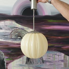 Super smuk art deco-lampe fra 1920'erne i tykt, cremefarvet glas. Skærmen måler 25 cm i diameter og er i rigtig god stand med ingen misfarvninger/pletter eller ridser. Fatningen har pga. materialet mere patina (se detaljebilleder).