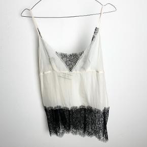 By Malene Birger hvid/sort blondetop / undertrøje i transparent materiale med bindebånd på ryggen.