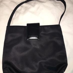Næsten ubrugt taske fra Benetton sælges. Grundet til salg er, at jeg ikke får den ellers så fine taske brugt.  Tasken har en ridse på flappen, der lukker tasken. Derudover er den så god som ny.