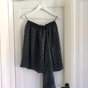 Sælger den e smukke elegante nederdel for designers remix! Nederdelen har den fineste detalje i siden som giver enorm elegance når man har den på! Perfekt med en plain top og stilletter! Stoffet er glans 🌼 nederdelen er helt ny med prismærke