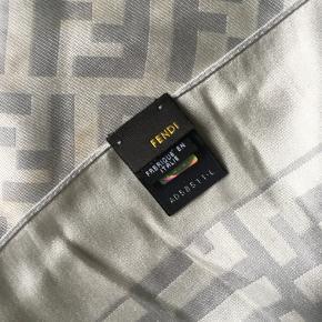 Ægte Fendi silketørklæde str. 45x45cm. Super smuk i en hvid farve med lysegrå monogram. Har få brugsspor, men ellers i fin stand. Da det er vintage kan der være små pletter, men disse er ikke tydelige.