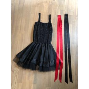 Jeg har brugt den som dansekjole.   Der er både et rødt og et sort bånd til at binde omkring maven.