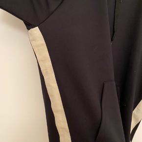 Mads Nørgaard hættetrøje.  Med lomme foran og hætte bagpå.  Har hvid stribe i siden.