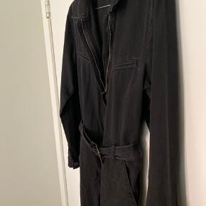 Fed sort denim buksedragt med lynlås og binde bælte. Lommer i bukserne og lige ben Stoffet er blødt og af tynd format i forhold til det er denim.  Lækker at have på.  Lincoln modellen