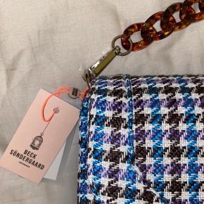 Skøn Beck Söndergaard taske, med god plads.  Tasken er i blå, lilla, råhvid og lidt brun💜💙🤎🤍 Jeg har aldrig fået taget den i brug, og derfor vil jeg nu prøve at sælge den.  Som sagt, er der stadig prismærke på, og derudover følger det en rem, så den også kan bæres crossbody!🤗 Skriv endelig for flere billeder!  Kom også gerne med et bud!💜💙