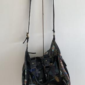 Sort stof skulder taske med mønster og mange lommer fra Desigual. Kan både bruges som skulder taske og håndtaske. Tasken er brugt men stadig i fin stand. Højde 32 cm og bredde 37 cm.
