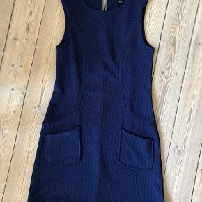 Super flot, tætsiddende kjole i god kvalitet.  Pænt snit med to lommer og en lynlås.  Næsten ikke brugt, fremstår derfor næsten som ny.  Mål.  Længde: ca. 82 cm. fra krave til kant, Bredde: ca. 34 cm.  Kjolen er lavet af 95% polyester og 5% elastane