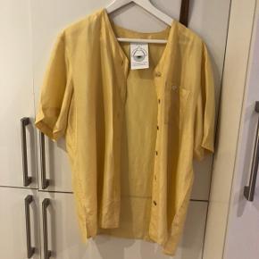 Kortærmet skjorte i en smuk lys eller pastel gul farve, som kan ses på billede nummer 2. Fitter en S-M men er oversize.