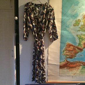 Fin kjole i blødt silke-agtigt polyester. Trekvartærmer, bindebånd og slå-om-effekt. Meget normal i størrelsen. Køber betaler fragt.  Bytter ikke.