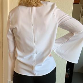 Elegant bluse med flotte ærmer i behageligt stof, der kan give sig lidt. Lukkes med lynlås på ryggen. Sælges da jeg ikke får den brugt.