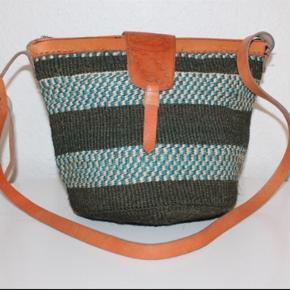 Smukke, håndlavede sisaltasker med detaljer i ægte læder fra Kenya. Læderrem kan justeres til den ønskede længde. Åbningen på tasken er ca. 35 cm. Den er foret indvendigt. Der er lynlås!   * Kan efter aftale afhentes i Brønshøj eller i Tølløse * Kan sendes, køber betaler porto