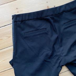 """""""Læder"""" bukser med fake læder på fronten og stof på bagsiden. Bukserne har lynlås i siden og en lille hægte, samt lomme detaljer bagpå (syet sammen). De går ca. til navlen (+/-).   Brugt få gange.   Afhentes på Nørrebro eller sendes på købers regning."""