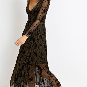 Smuk slå-om kjole i sort med guld glimmer og blomster detaljer i sort velour. Sidder så fint på. Kjolen har gennemsigtige ærmer og ellers er der en inderkjole der er syet fast. Brugt max 4 gange og fremstår som ny. Super cool med et par Doc's til.